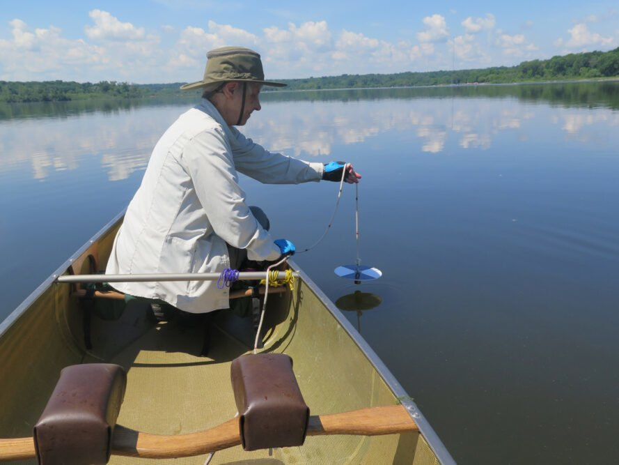 person in boat monitoring lake pollution