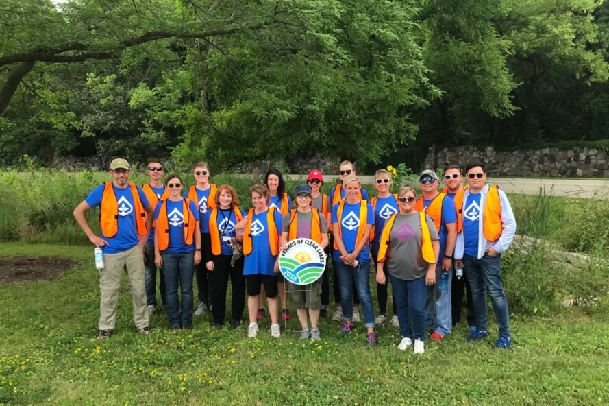 volunteers in orange vests standing in a group and smiling