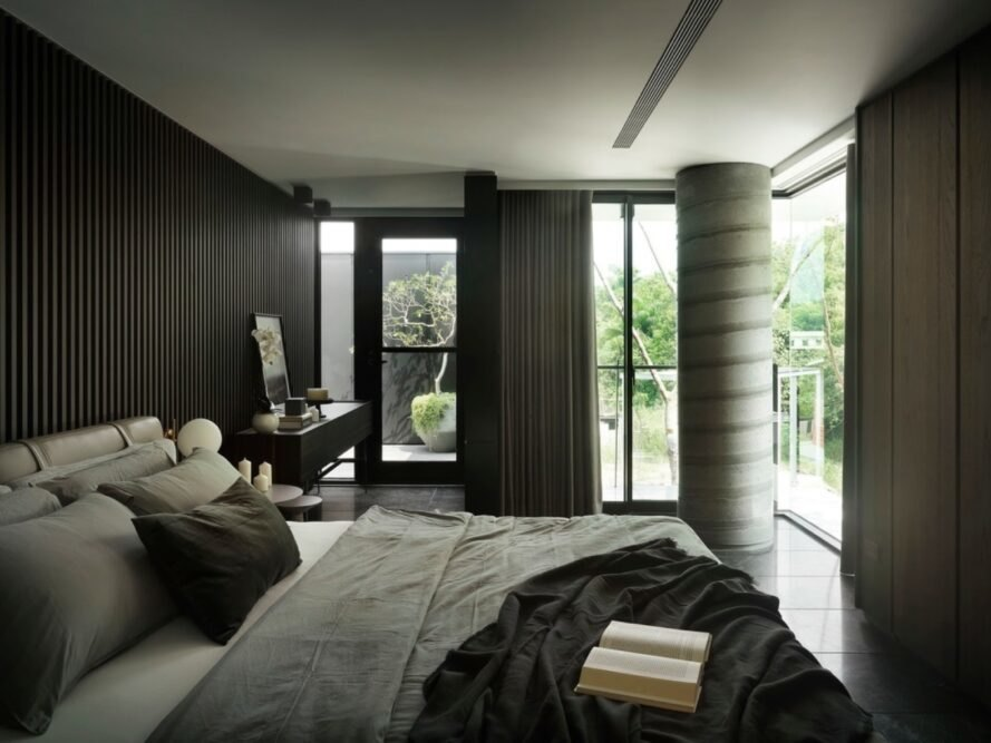 gray bed facing wood paneled wall
