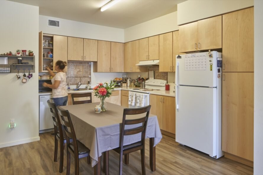 apartment kitchen with dining table and wood cabinets