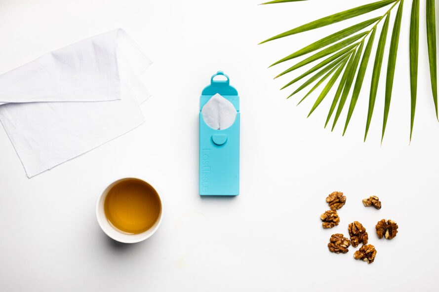 a flat lay of the turquoise case open and showing a tissue sticking out. to the left is a tissue laid out, with a cup of tea below it. to the right is a green leaf and below it are scattered walnuts for decoration.