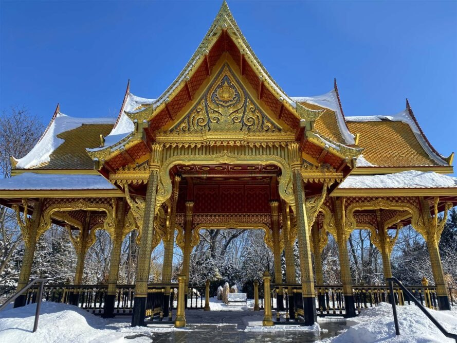 a bright gold and red piece of Thai architecture surrounded by snow