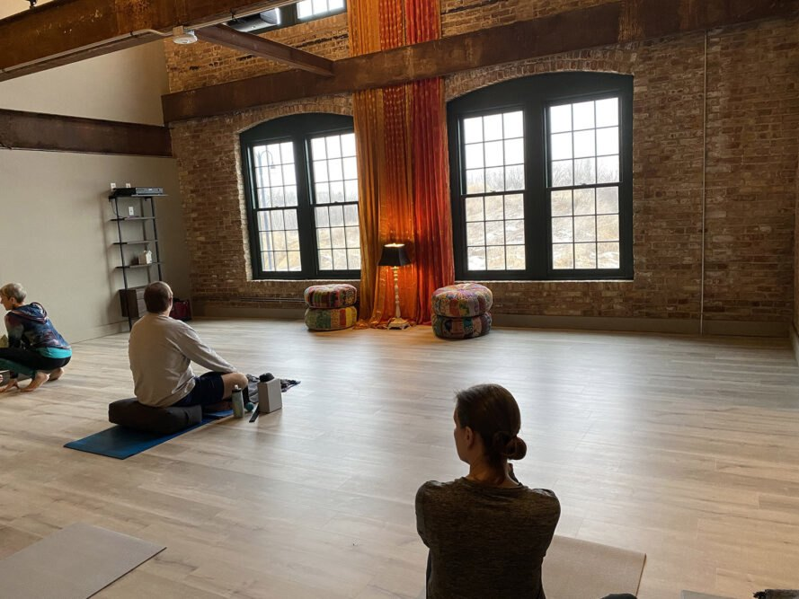 the inside of a yoga studio with people sitting, waiting for instruction