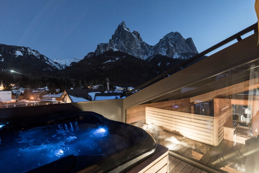 hot tub on a wood balcony with mountains in the distance