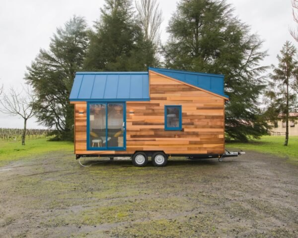 tiny wooden home with aluminum blue roof