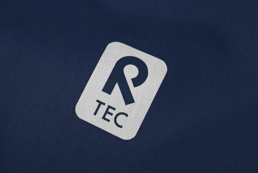 """silver label that reads, """"R TEC"""" on a blue jacket"""