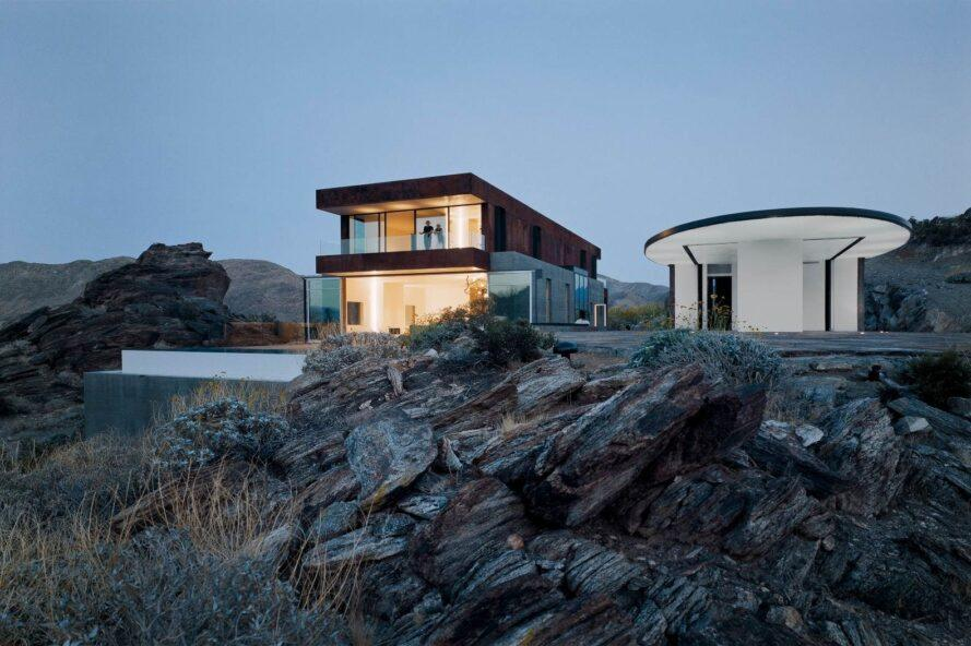 two-story home illuminated from within at dusk