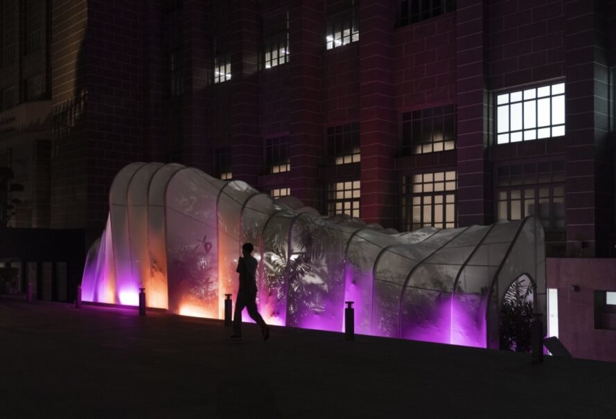 white nylon pavilion lit with purple and red lights at night