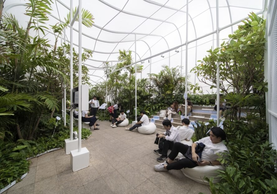 people lounging near plants under a white nylon pavilion