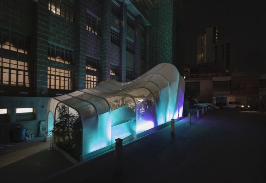 white nylon pavilion lit with blue lights at night