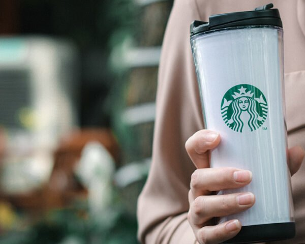 person holding white Starbucks-branded reusable cup