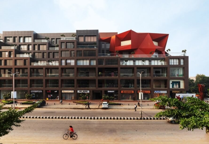 brown office building topped with a red geometric facade
