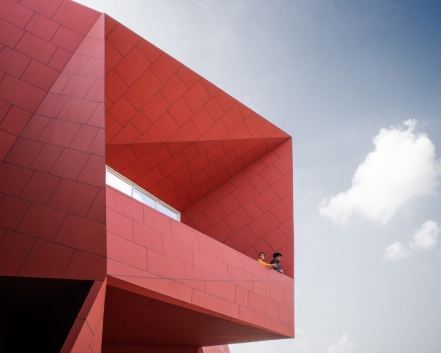 red geometric facade with a huge window
