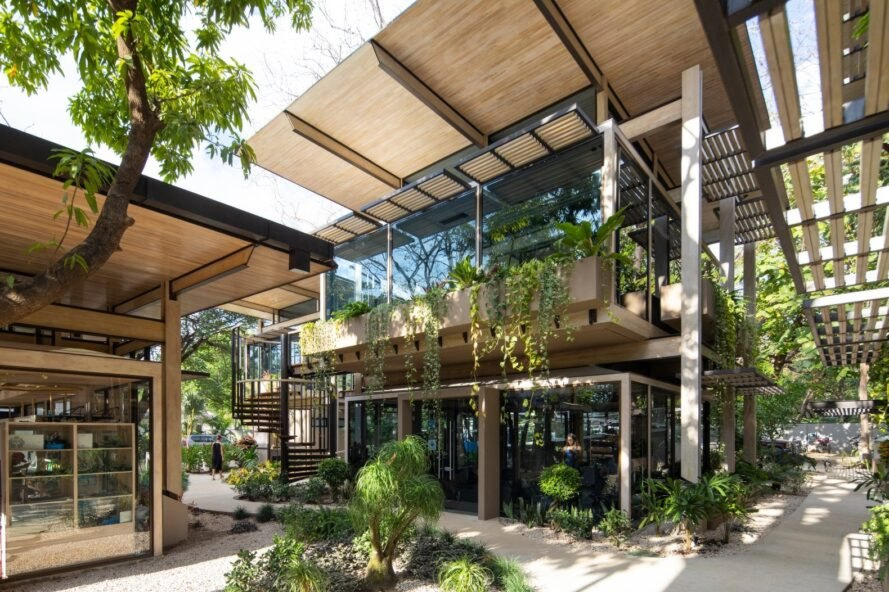 glass building surrounded by greenery