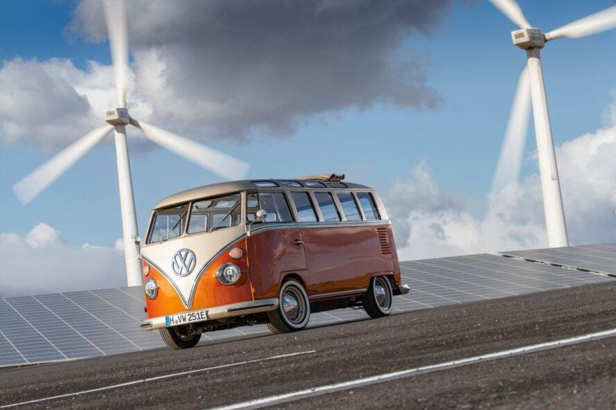 Orange VW van on the road with windmill in the background