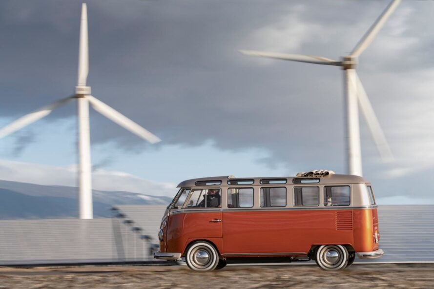 VW van driving past windmills