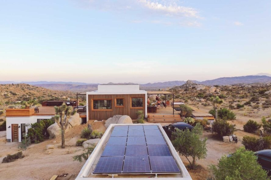 elongated solar array with tiny home in the background