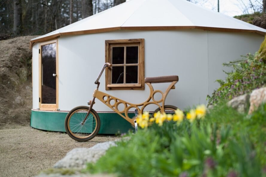 bicycle leaning up against a white yurt