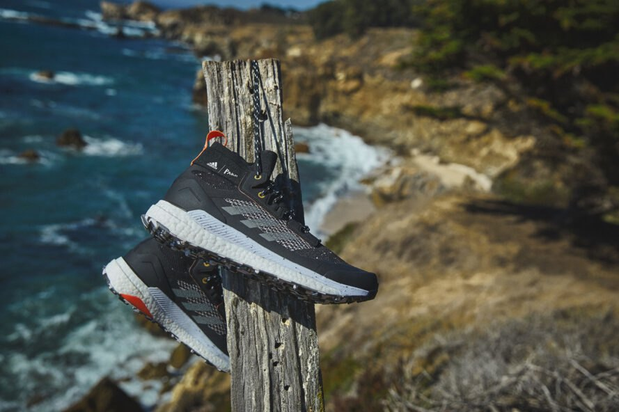 black Adidas hiking sneaker hanging from a wood pole