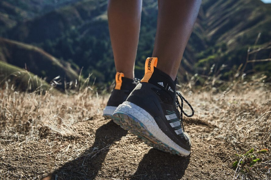 person in black Adidas hiking shoes walking a dirt trail