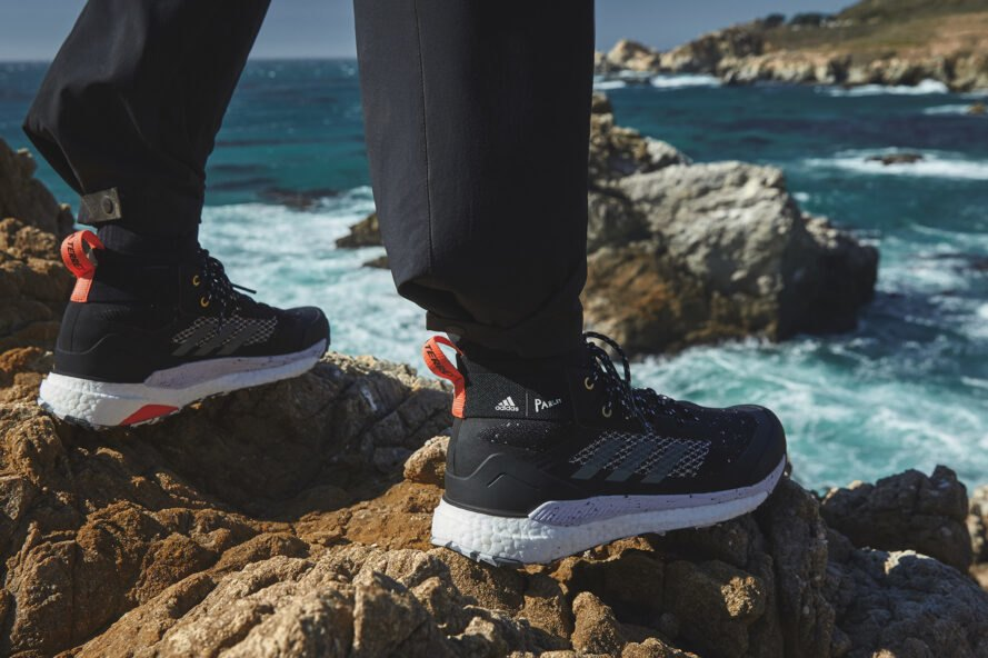 person in black Adidas standing on a rock overlooking the ocean