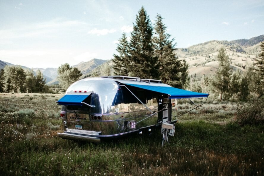 shiny airstream trailer with blue awnings