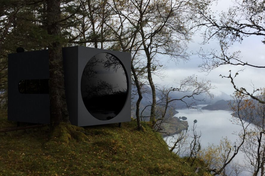 black cubic cabin with a large round window overlooking a river