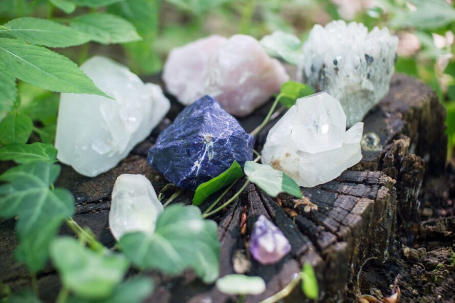 various crystals on a tree stump surrounded by leaves