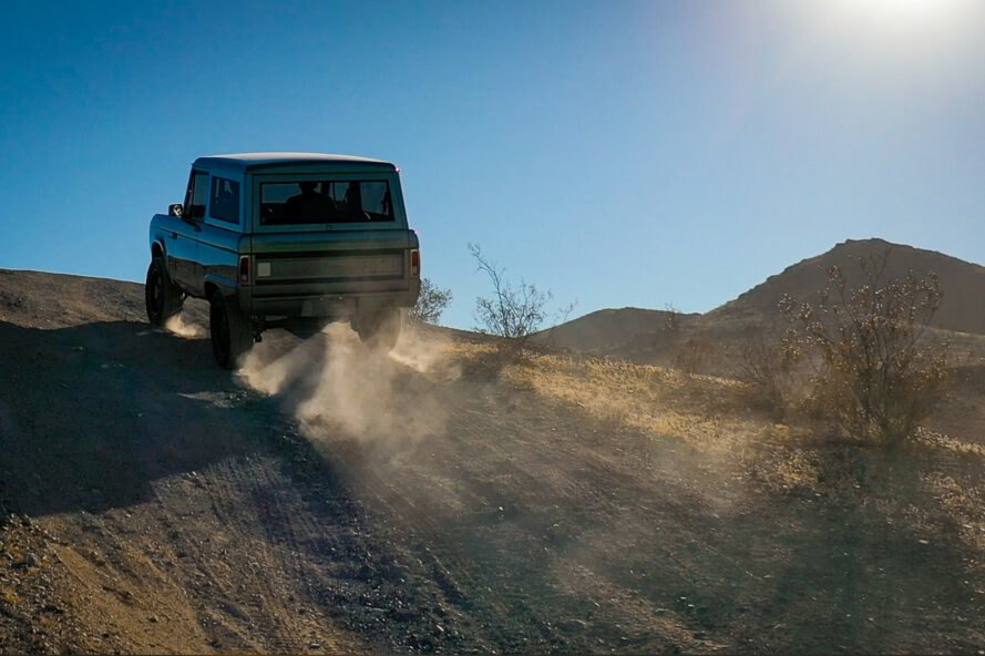 trail of dust left behind a Ford Bronco driving up a hill