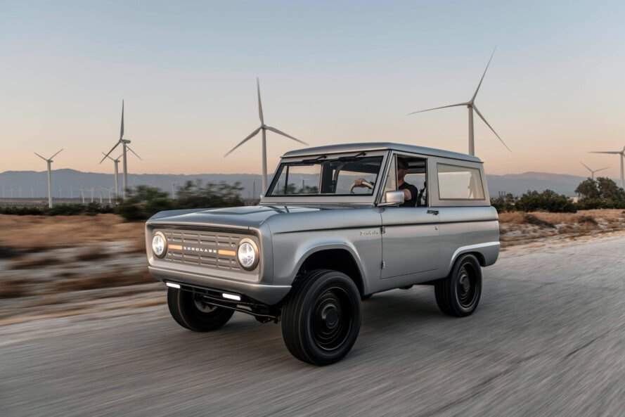 windmills behind a silver Ford Bronco