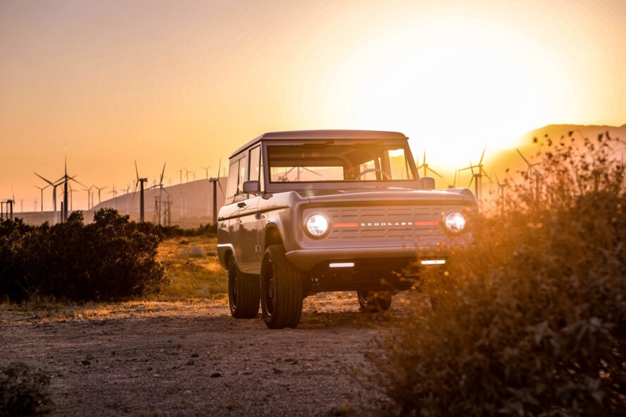 Ford Bronco driving on a dusty road at sunset