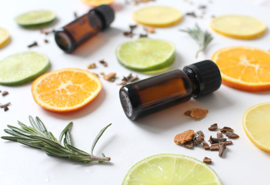 small brown essential oil bottles surrounded by slices of orange, lime, seeds and herbs