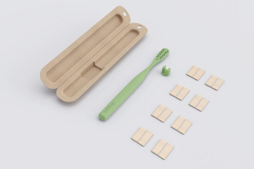 green toothbrush next to flat bamboo bristles and a compostable container