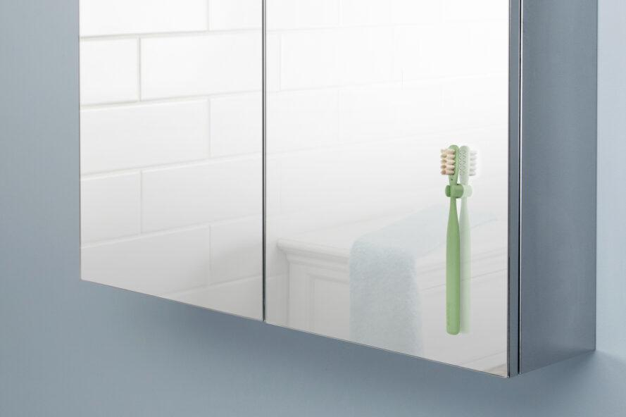 green toothbrush hanging on a mirror