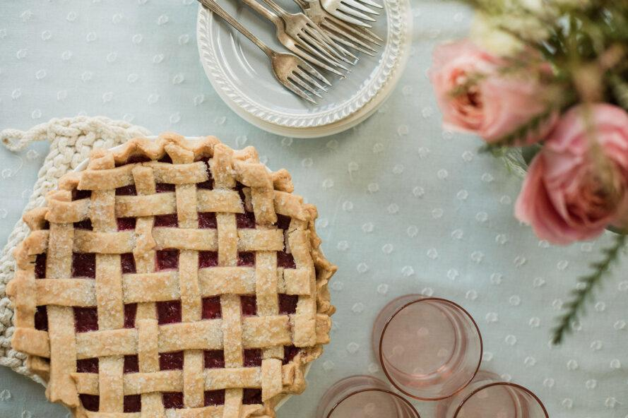 aerial view of pie near pink cups and a vase of pink flowers
