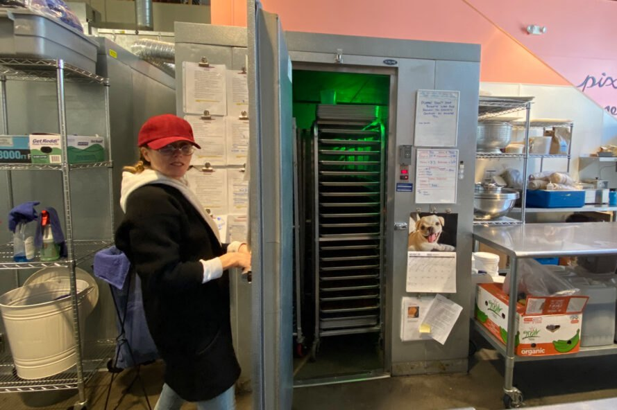 person opening door to commercial refrigerator
