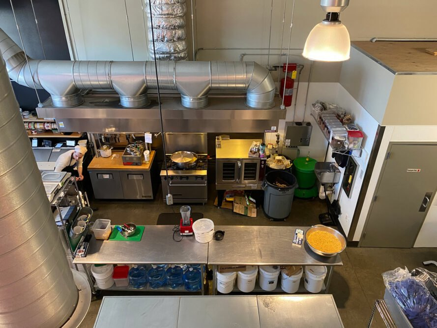aerial view of commercial kitchen with stainless steel tables and appliances