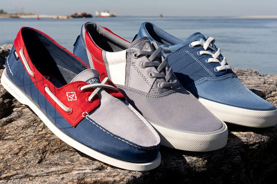 red, gray and blue boat shoes on a rock with water in the background