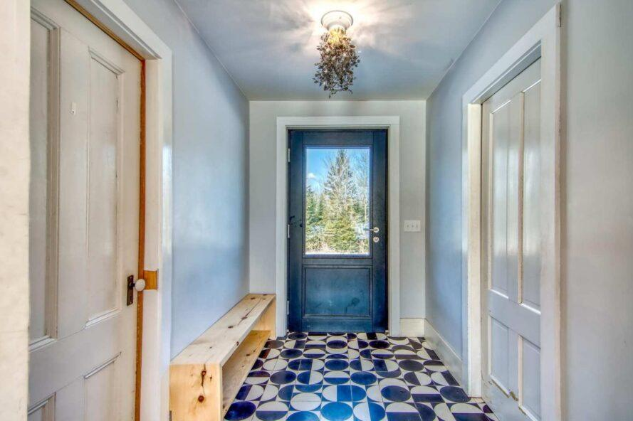 entryway with dark front door, white walls and patterned floors