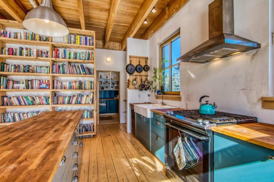 kitchen with blue cabinets and floor-to-ceiling shelves of a pantry