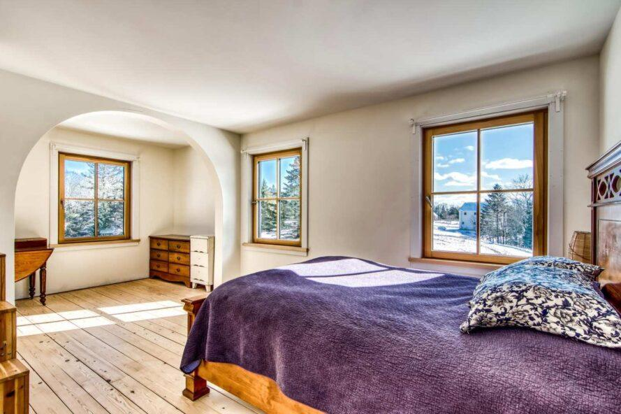 bedroom with large windows and purple bed