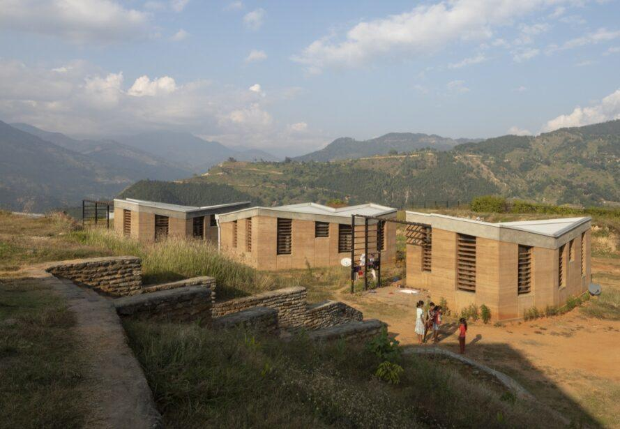 aerial view of rammed earth hospital buildings with mountains in background