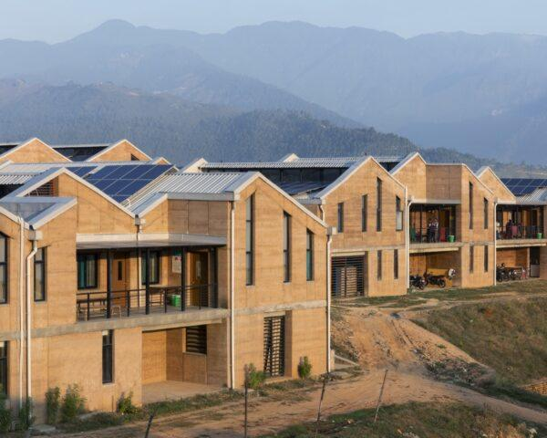 several rammed earth buildings with solar panel roofs