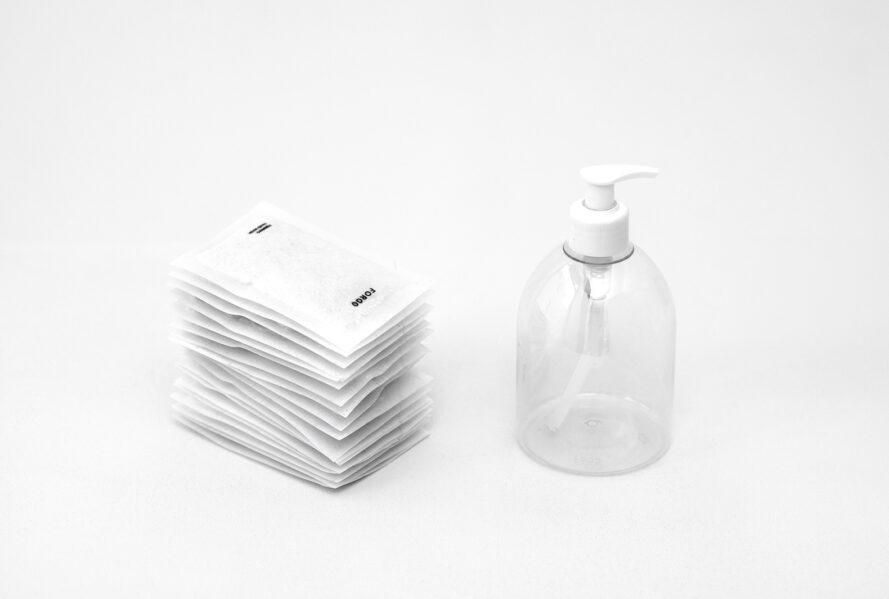 packets of powder soap next to a clear plastic bottle