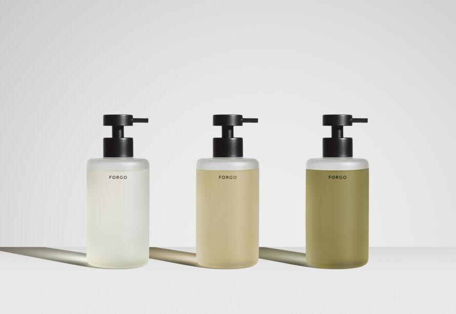 three bottles of FORGO soap in clear, light peach, and olive green colors