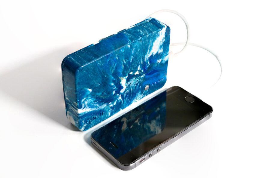 a blue and white marbled external charger connect to a smartphone