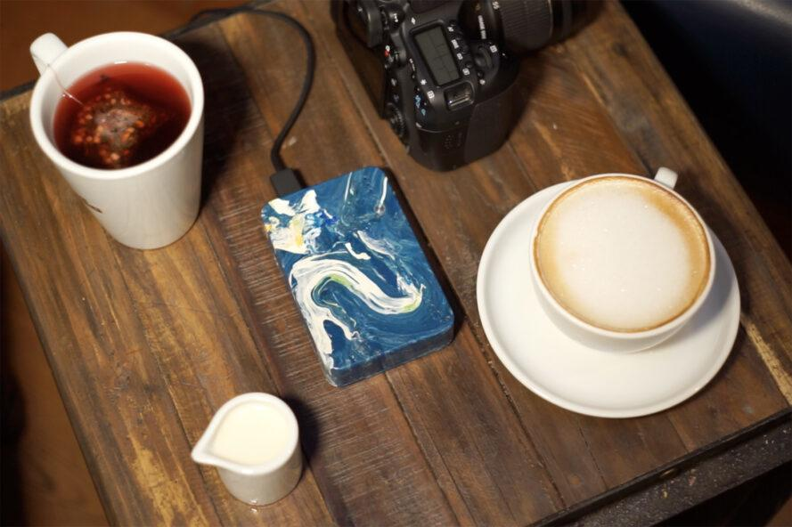 a blue and white marbled external charger connected to a camera next to cups of coffee and tea on a wood table