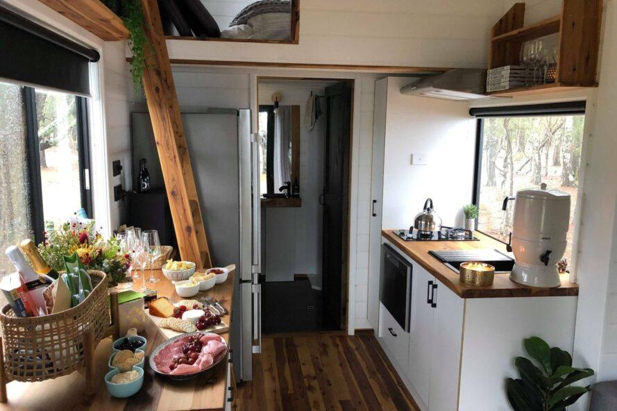 tiny home kitchen with white cabinets and wood countertops