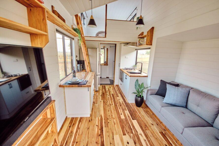 tiny home interior with white walls, cypress flooring and a gray sofa