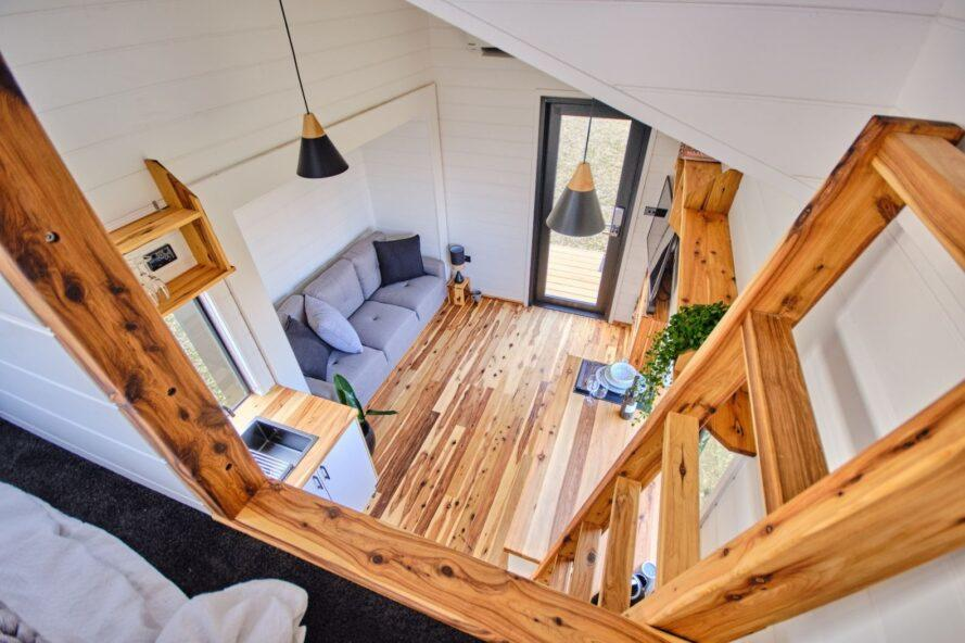 aerial shot of interior living space in tiny home with white walls and wood floors